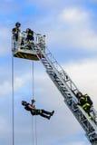 Feuerwehrmänner auf hinterer Plattform und einem Feuerwehrmann, der ein Seil hinuntergeht Stockfotografie