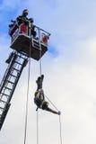 Feuerwehrmänner auf hinterer Plattform und einem Feuerwehrmann, der ein Seil hinuntergeht Lizenzfreies Stockbild
