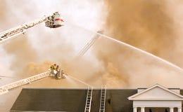 Feuerwehrmänner auf Strichleiterplattform Stockfotografie