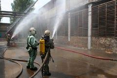 Feuerwehrmänner in den chemischen Schutzklagen und in den Gasmasken Lizenzfreie Stockfotografie