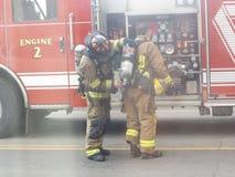 Feuerwehrmänner, die bis zu den Kampffeuern entsprechen lizenzfreies stockbild