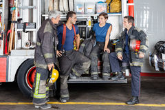 Feuerwehrmänner, die an der Feuerwache sich unterhalten Stockfotografie