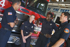 Feuerwehrmänner, die durch ein Löschfahrzeug plaudern stockfotos