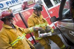 Feuerwehrmänner, die ein Auto schneiden, um zu helfen verletzt Stockbild