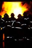 Feuerwehrmänner, die ein Feuer in Angriff nehmen Lizenzfreie Stockbilder