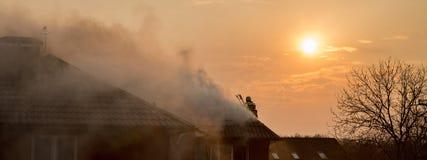 Feuerwehrmänner, die ein rasendes Feuer mit enormen Flammen des brennenden timbe kämpfen lizenzfreie stockbilder