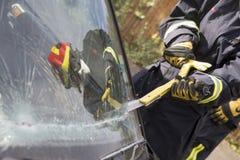 Feuerwehrmänner, die einen Autowindfang brechen Stockfotografie