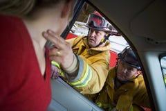 Feuerwehrmänner, die einer verletzten Frau in einem Auto helfen stockfotos