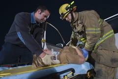 Feuerwehrmänner, die einer verletzten Frau helfen Lizenzfreie Stockbilder