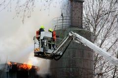 Feuerwehrmänner, die Feuer auf hydraulischem Crane Platform auslöschen Stockbild