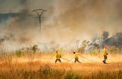 Feuerwehrmänner, die Feuer kämpfen stockfotos