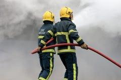 Feuerwehrmänner, die Feuer mit Schlauch kämpfen Lizenzfreies Stockfoto