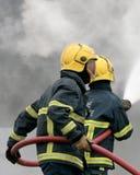 Feuerwehrmänner, die Feuer mit Schlauch kämpfen Stockbild