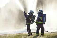 Feuerwehrmänner, die gegen Hintergrund von waterdrops sprühen stockfotografie