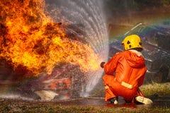Feuerwehrmänner, die Hochdruckwasser sprühen, um abzufeuern Stockbilder