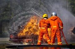Feuerwehrmänner, die Hochdruckwasser sprühen, um abzufeuern, feuerbekämpfend Stockfoto