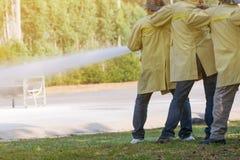 Feuerwehrmänner, die Löscher und Wasser vom Schlauch für Feuerbekämpfung verwenden Lizenzfreie Stockfotografie
