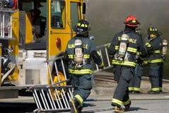 Feuerwehrmänner, die Strichleiter anhalten Stockfotos