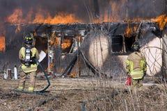 Feuerwehrmänner, die vor einem brennenden Haus stehen Stockbilder