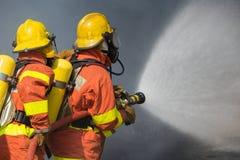 2 Feuerwehrmänner, die Wasser in der Feuerbekämpfung mit dunklem Rauche b spritzen Lizenzfreie Stockfotos