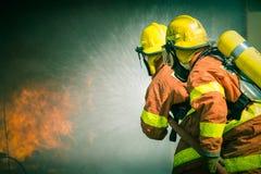 2 Feuerwehrmänner, die Wasser im Film- Ton sprühen stockfotos