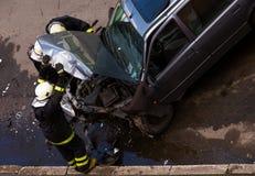 Feuerwehrmänner, die zerschmettertes Auto überprüfen lizenzfreie stockbilder