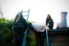 Feuerwehrmänner in einer speziellen Form auf dem Dach eines brennenden Hauses Stockfoto
