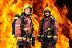 Feuerwehrmänner gegen brennenden Hintergrund Stockfotografie