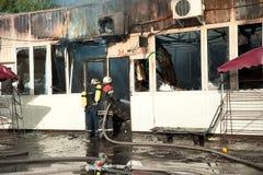 Feuerwehrmänner löschen das Feuer in einem Lager mit Wasser aus Lizenzfreie Stockfotos