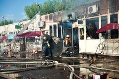 Feuerwehrmänner löschen das große Feuer in einem Lager aus Stockbild