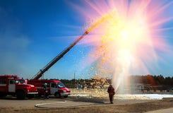 Feuerwehrmänner löschen die Sonne mit Schaum aus und wässern Lizenzfreies Stockfoto