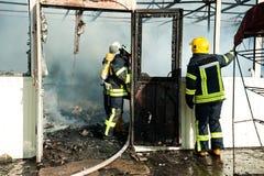Feuerwehrmänner löschen ein großes Feuer an Troyeschina-Markt mit Wasser und Feuerlöschern aus Lizenzfreies Stockfoto