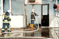 Feuerwehrmänner löschen ein großes Feuer an Troyeschina-Markt mit Wasser und Feuerlöschern aus Stockbild