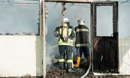 Feuerwehrmänner löschen ein großes Feuer an Troyeschina-Markt mit Wasser und Feuerlöschern aus Stockfoto