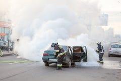 Feuerwehrmänner löschen gebranntes Auto in der Stadt Stockfotos