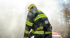 Feuerwehrmänner mit einem Schlauch in der Aktion Stockfoto