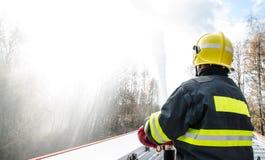 Feuerwehrmänner mit einem Schlauch in der Aktion Stockfotos