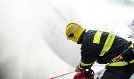 Feuerwehrmänner mit einem Schlauch in der Aktion Stockfotografie