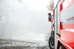 Feuerwehrmänner mit einem Schlauch in der Aktion Stockbilder
