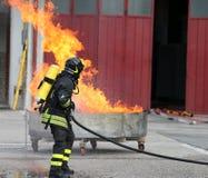 Feuerwehrmänner mit Sauerstoffflaschen weg vom Feuer während eines Trainings Lizenzfreies Stockbild