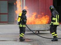 Feuerwehrmänner mit Sauerstoffflaschen weg vom Feuer während eines Trainings Lizenzfreie Stockfotos
