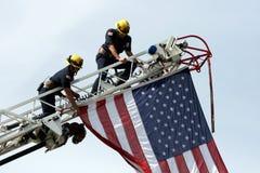 Feuerwehrmänner mit USA-Markierungsfahne lizenzfreies stockbild