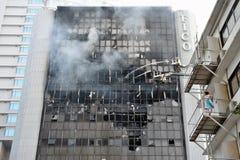 Feuerwehrmänner packen eine Flamme in einem Büro-Block an stockbilder