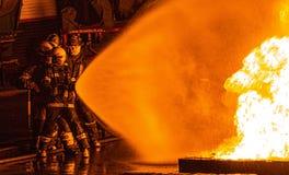 Feuerwehrmänner, welche die Linie halten lizenzfreie stockfotos