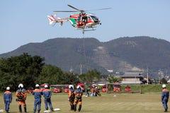 Feuerwehrmann arbeitet mit einem Hubschrauber Lizenzfreie Stockfotos