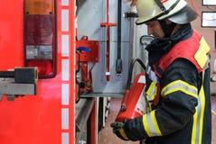 Feuerwehrmann auf dem Löschfahrzeug mit einem Feuerlöscher Lizenzfreies Stockbild