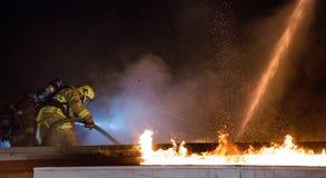 Feuerwehrmann in der Aktion auf dem Dach Stockfotografie