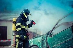 Feuerwehrmann, der brenzlige Stelle mit Wärmekamera überprüft stockbild