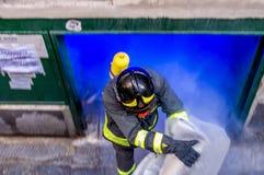 Feuerwehrmann, der den brennenden Plastik aus einer Lagerung auf Feuer heraus herausnimmt Lizenzfreies Stockfoto