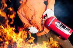 Feuerwehrmann, der ein rasendes Feuer mit großen Flammen kämpft Lizenzfreies Stockbild